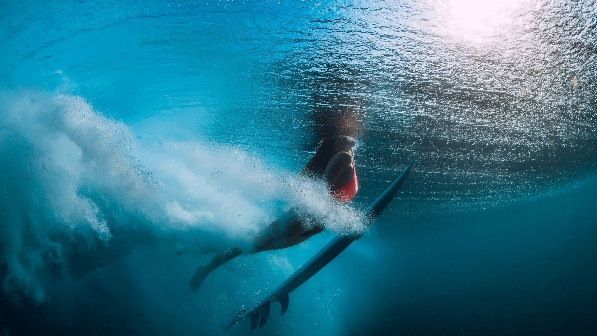 duck dive of a girl surfing